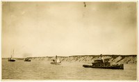 Water view of three steam-powered cannery tenders and steamship