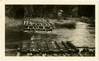 Partially-constructed crude bridge sits on either side of small river with mouth of cave in background