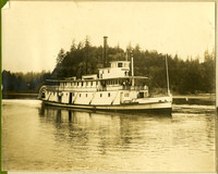 """Wooden stern-wheeler """"Fairhaven"""" with several peole on deck moves through water with forested hills in background"""