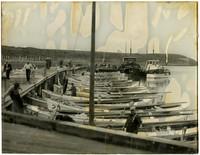Many small, single-masted fishing boats moored at pier, with three larger fishing boats