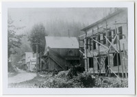 Glacier Hotel under construction with scaffolding on its front, and other buildings along the street, Glacier WA