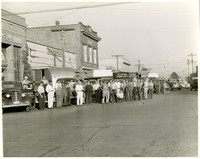 Large group of men pose in front of row of trucks parked on main street, Ferndale, Washington