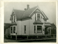 Side and front exterior view of Queen Anne-style house with small yard