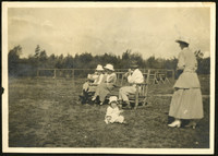 A little girl sits on the ground outdoors with a woman standing near and three people on bench