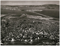 Aerial view from Oakland - By Moulin - Showing San Francisco-Oakland Bay Bridge, Golden Gate Bridge and  man-made Treasure Island at upper center, showing a sketch of the Golden Gate International Exposition layout