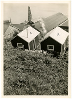 View from hillside above of rooftops of cabins, warehouses, and buildings with water beyond