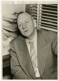 Close-up of unidentified man in suit, sitting in office with desk and papers behind him