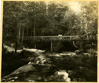 Two women stand in the middle of a rustic bridge spanning Whatcom Creek in Whatcom Falls Park.