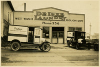 "Two early-model motorized delivery vans are jpared in front of ""DeLuxe Laundry"" building"
