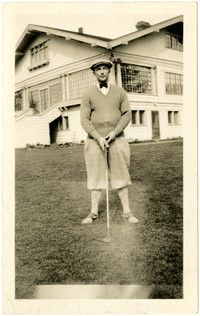 Man in golf attire posing with golf club
