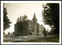 Imposing three story brick Columbia School building with belltower