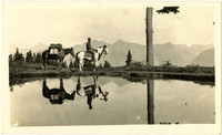 Man on pinto pony leading pack horse is reflected in lake in foreground
