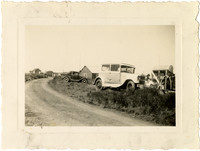 Dirt road with cars parked in brush at roadside with small houses in background at Pacific American Fisheries cannery at Naknek, Alaska
