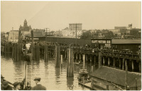 First run of the Bellingham ferry, Victoria. View from deck of ship of large crowd gathered on Quackenbush Warehouse dock, with city of Bellingham, WA, in background