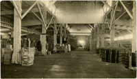 Interior of port dock warehouse with bags, boxes, and barrels of goods