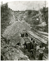 A crew of workers clears rock and lays railroad at foot of hillside that has been blasted away for road or rail construction or for quarry operation