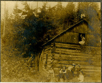 A group of men, women, and children pose in front of and around log cabin in woods
