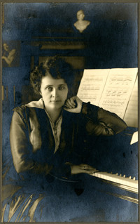 Elegantly dressed Madame Engberg, Beck Theater Director, poses at a piano.