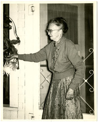 Elderly woman stands in profile in front of house screen door, reaching towards hanging potted plant