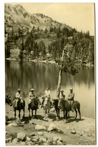Four men and one woman on horseback pose in front of alpine Picture Lake