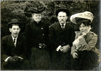 Two men and two women in coats and hats seated in front of trees