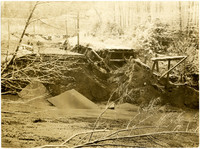 Collapsed road and railroad bridges at river's edge