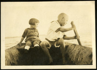 A little by and little girl sit in row boat on lake