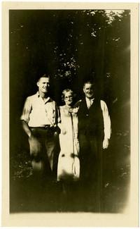 A woman stands between two men in dappled light