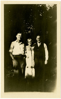 A woman stands between two men in dappled light