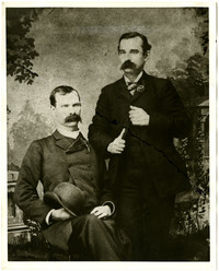 Two unidentified men, seated and standing, wearing suits in studio portrait