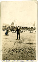 Man poses on beach with crowds and The Cliff House in background
