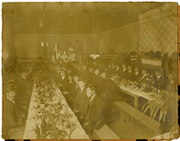 Banquet hall with two long, well-appointed tables seating several dozen men in suits