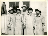 Four smiling women in rain gear, with a man standing behind with his arms resting on their shoulders