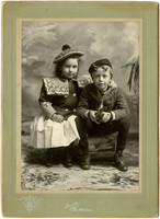 Young girl and young boy sit in studio portrait
