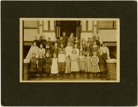 School children pose in three rows on steps of school