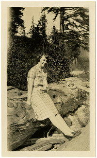 Woman poses on large log on beach