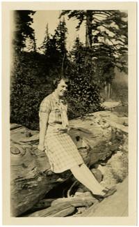 Woman poses on large log on beach