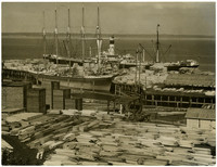 Docks covered with piles of cut lumber, with freight vessels moored in background