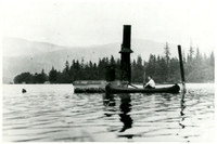 A man canoes past the mast, stacks, and upper wheelhouse of a sunken ship on Lake Whatcom