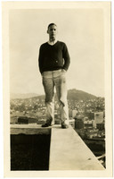 David C. Morse, a young man, stands atop the southeast corner of the B.B. Furniture Building, with downtown Bellingham, WA, visible below