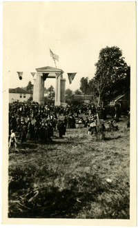 People gathered at the Peace Arch with Canadian structures in background