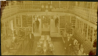 Interior of mercantile with view from upper level looking down onto main floor with display cases and several clerks