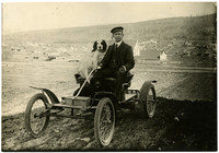 A man sits with two dogs in simple, early automobile, Larrabee Avenue at 19th street