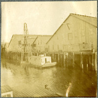 Pile-driving scow is moored next to warehouse dock