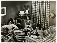 Unidentified college dorm room or hotel room scene with three young women