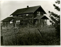Exterior of two-story farmhouse seen from across small field