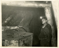 Miner with headlamp standing in mine shaft next to coal shute.