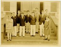 Uniformed boys choir on steps of Lowell School with teacher Grace Sullivan, 1928