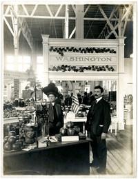 Interior of pavilion with two people standing in Washington section of produce on display