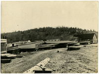 Several boats rest in drydock on beach